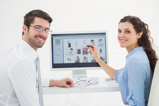 Portrait of smiling teamwork using computer
