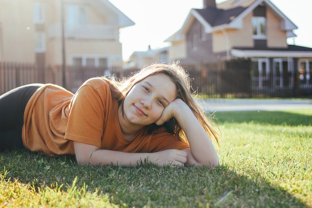 Portrait of smiling teen girl lying on sunny green grass of cottage village on background