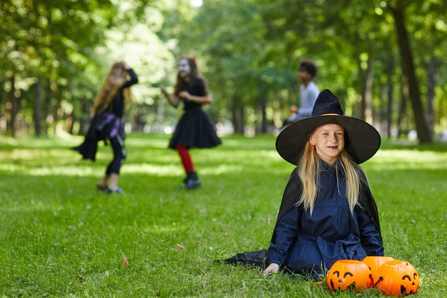 Portrait of smiling teenage girl dressed as witch for halloween sitting on green grass outdoors with kids playing in surface, copy space