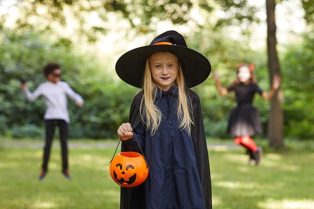 Portrait of smiling teenage girl dressed as witch posing outdoors and holding halloween bucket with kids playing in surface, copy space