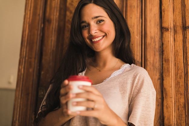 Portrait of a smiling teenage girl holding disposable coffee cup