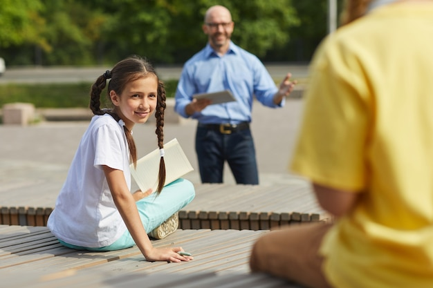 Portrait of smiling teenage girl looking over at classmate while enjoying outdoor lesson in sunlight with male teacher in background, copy space