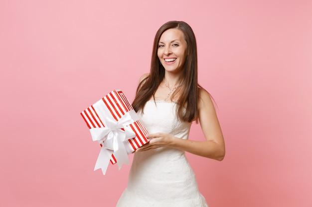 Ritratto di donna tenera sorridente in bellissimo abito bianco che tiene in mano una scatola rossa con un regalo regalo