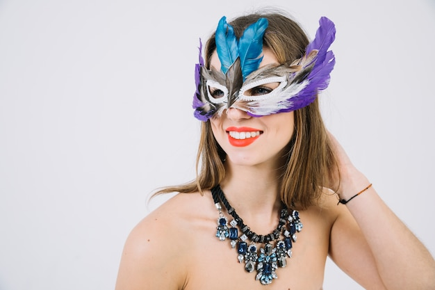 Portrait of a smiling topless woman wearing feather mask