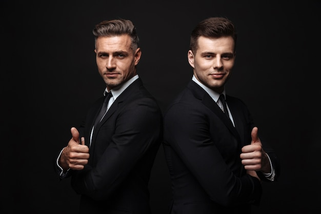 Portrait of smiling two businessmen dressed in formal suit posing at camera back to back with thumb up isolated over black wall