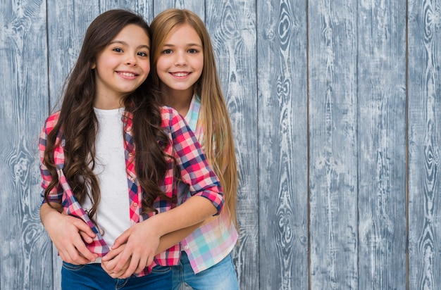 Portrait of smiling two pretty girls standing against grey wooden texture wall