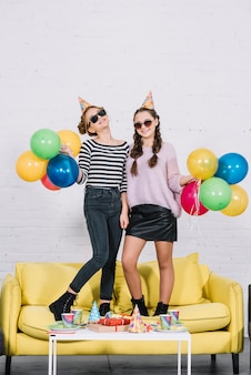 Portrait of smiling two teenage girls standing on yellow sofa holding colorful balloons in hand