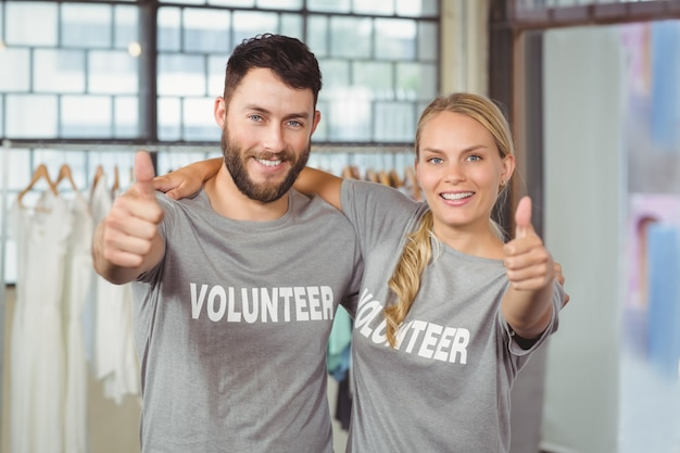 Portrait of smiling volunteers giving thumbs up in office