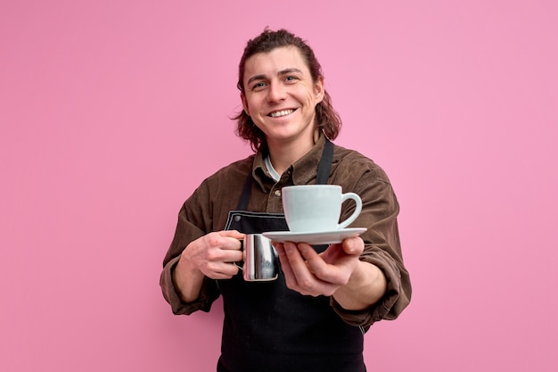 Portrait of smiling waiter guy student work part-time in coffee bar shop give to client mug of coffee