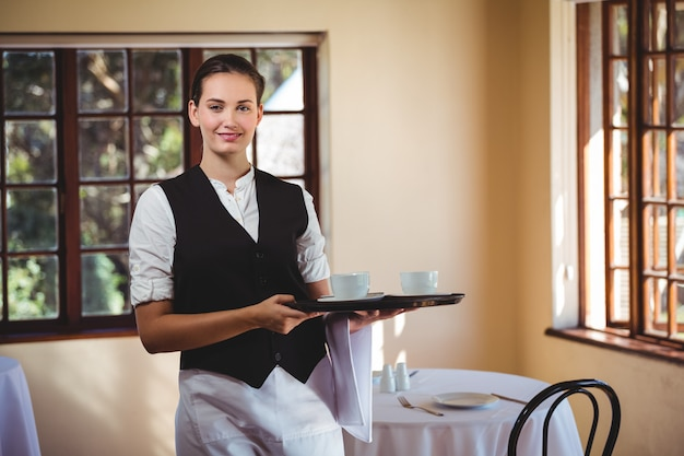 Portrait of smiling waitress holding a tray of coffee cups