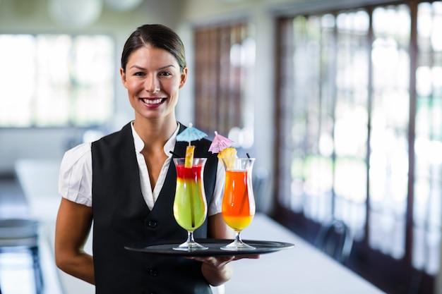 Portrait of smiling waitress serving cocktai