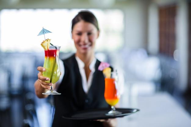 Portrait of smiling waitress serving cocktail