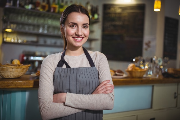 Portrait of smiling waitress standing at counter