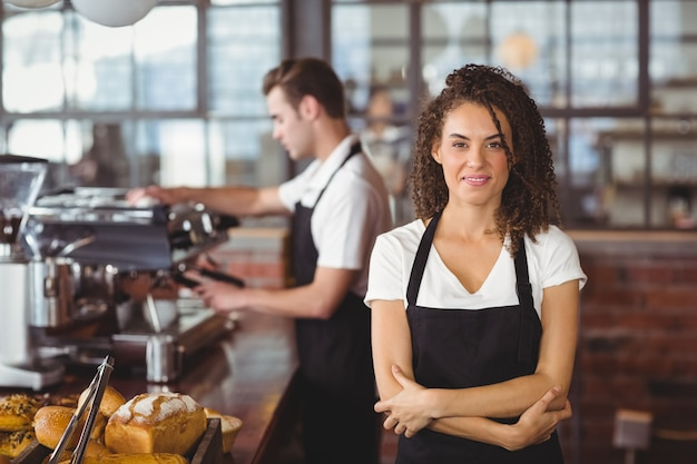 Portrait of smiling waitress with arms crossed in front of colleague at coffee shop