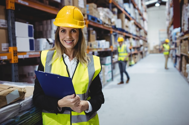 Portrait of smiling warehouse manager holding clipboard