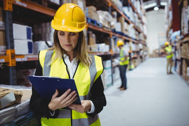 Portrait of smiling warehouse manager looking at clipboard