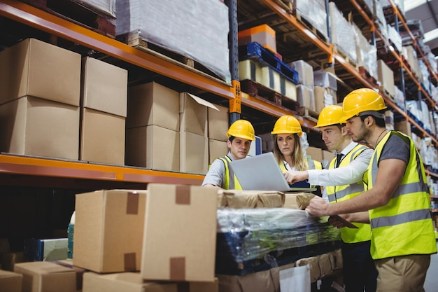 Portrait of smiling warehouse managers using laptop