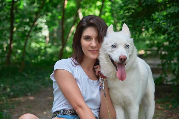 Портрет улыбается женщина и игривая собака