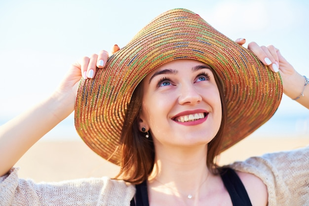 Portrait of smiling woman on beach wearing straw hat