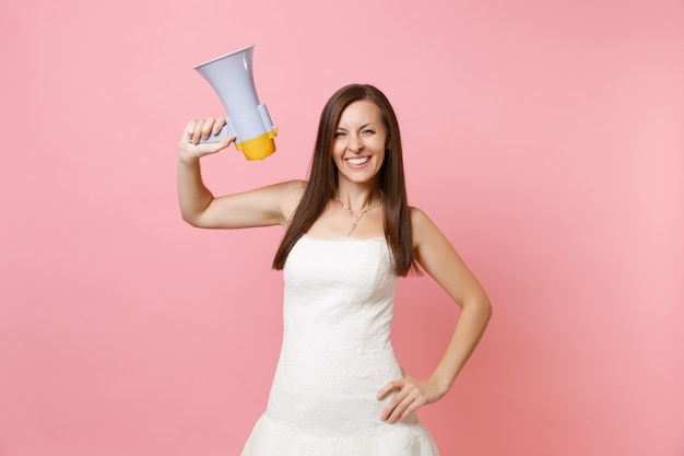Portrait of smiling woman in beautiful white lace white dress standing and holding megaphone
