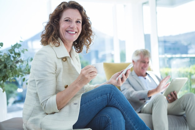 Portrait of smiling woman by man holding mobile phone