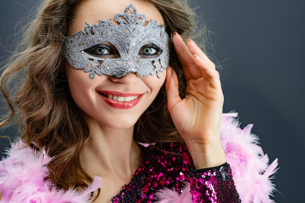 Portrait of a smiling woman in carnival masks looking at the camera close-up