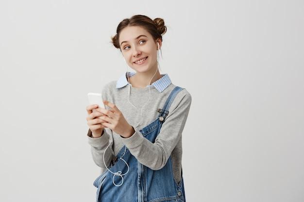 Ritratto della donna sorridente in tuta del denim che guarda lateralmente con gli occhi ingannevoli. con le cuffie. impiegato femminile divertente che chiacchiera con il suo collega che è civettuolo. sentimenti positivi