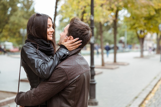 Portrait of a smiling woman embracing with her boyfriend outdoors