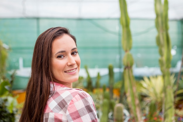 Portrait of smiling woman in greenhouse