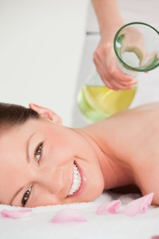 Portrait on a smiling woman having massage oil versed on her back