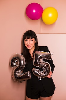 Portrait of a smiling woman holding 25 silver celebration balloon in hand