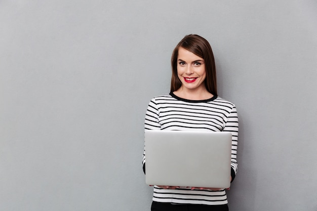 Portrait of a smiling woman holding laptop computer