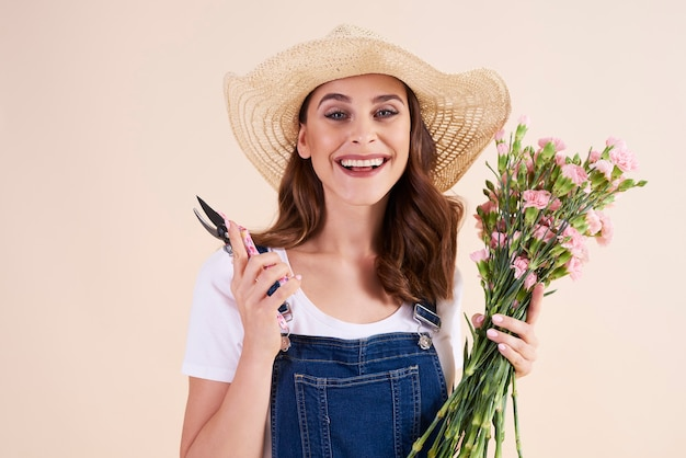 Portrait of smiling woman holding pruning shears and flowers