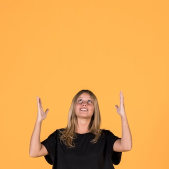 Portrait of smiling woman looking up and gesturing on yellow wall background