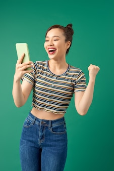 Portrait of a smiling woman making selfie photo on smartphone isolated on green