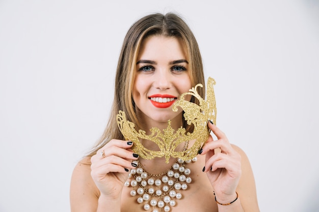 Portrait of a smiling woman in necklace holding golden carnival mask