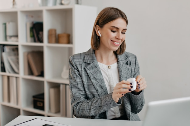 Portrait of smiling woman in office outfit putting on airpods to communicate with customers.