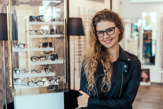 Portrait of smiling woman in optical store.