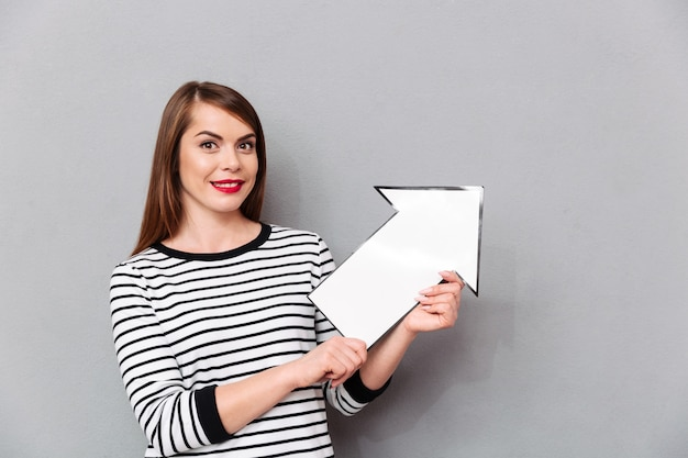 Portrait of a smiling woman pointing paper arrow up