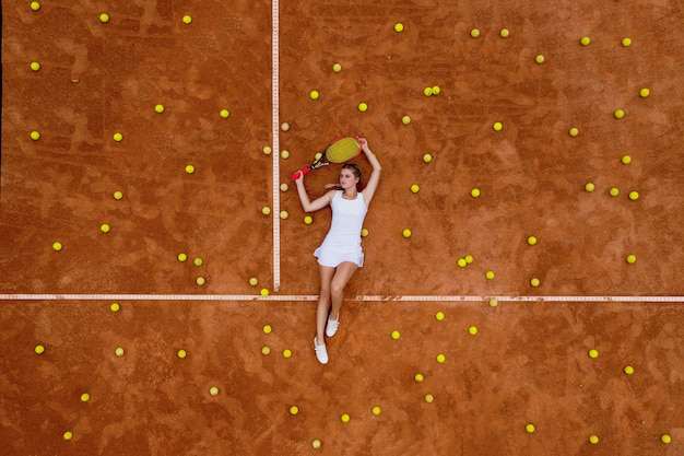 Portrait of smiling woman relaxing on tennis court with a lot of balls and racket after training