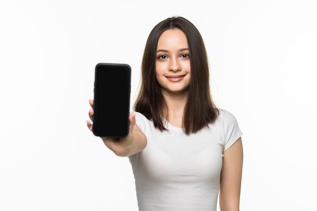 Ritratto di una donna sorridente che mostra lo schermo dello smartphone vuoto su un bianco