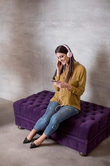 Portrait of smiling woman sitting and listening to music on headset