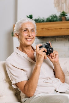 Portrait of smiling woman sitting on sofa holding camera