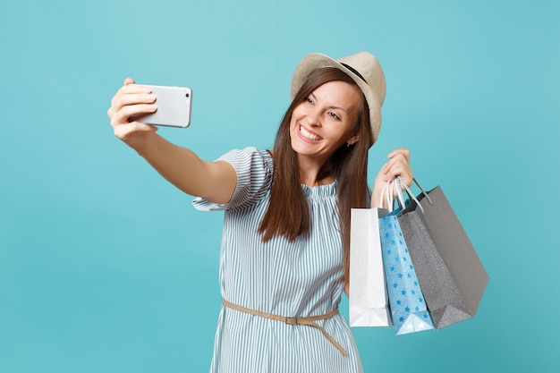 Portrait smiling woman in summer dress, straw hat holding packages bags with purchases after shopping doing selfie shot on mobile phone isolated on blue pastel background. copy space for advertisement