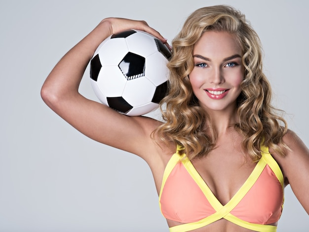 Portrait of a smiling woman in trendy swimsuit holds a soccer ball