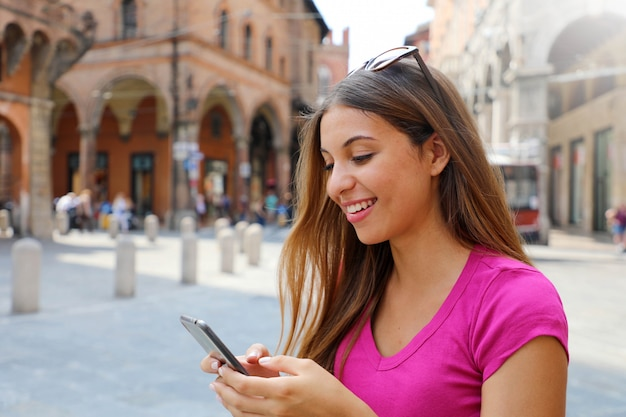 Portrait of smiling woman using smart phone in old medieval town