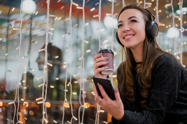 Portrait of smiling woman wearing headphones holding cup and phone near christmas lights