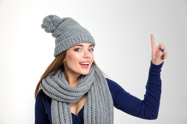 Portrait of a smiling woman wearing in scarf and hat pointing finger up isolated on a white background