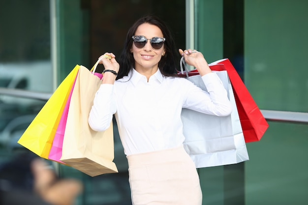 Portrait of smiling woman wearing stylish sunglasses and classic white blouse. beautiful model holding colorful bags in hands after going shops.