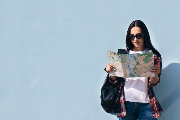 Portrait of smiling woman wearing sunglasses reading map and standing near blue wall